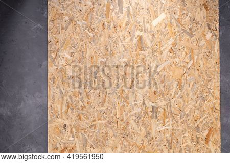 Wood osb background texture at concrete floor. Wooden chipboard at wall background with copy space