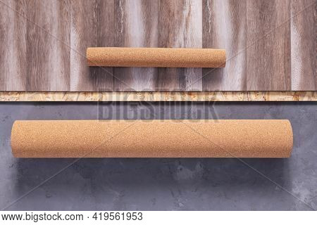 Cork roll and laminate floor on concrete background texture. Cork background at wooden laminate floor and chipboard