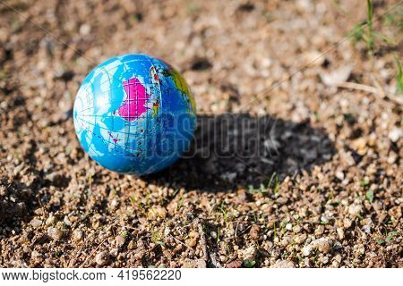 Globe Or Earth On Arid Soil With Sunlight. Saving  Protect, Environment, Arbor Day, Card For World E