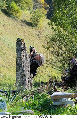 Senior Artist Carving In Large Stone With Enthusiasm Outside In Beautiful Green Nature.