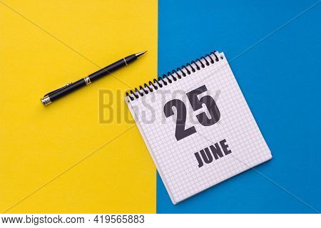 June 25th. Day 25 Of Month, Calendar Date. Notebook With A Spiral And Pen Lies On A Yellow-blue Back