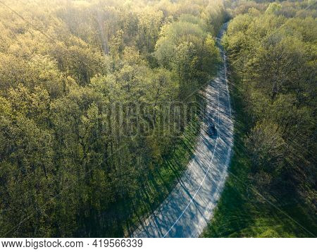 Car in summer time nature from air on Highway road in the forest. View from a drone. Aerial view.