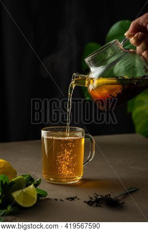 Woman Pouring Hot Black Tea