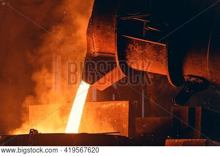 Molten Metal Pour From Big Container Into Sand Mold. Iron Casting In Metallurgy Foundry Plant, Heavy