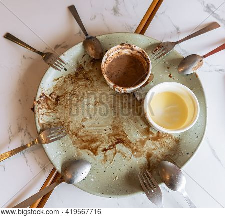 Empty Plate With Food Leftovers From Dessert Meal, Spoons And Forks On Marble Table. Dirty Plate Wit