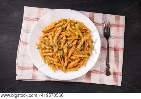 Penne Pasta In Tomato Sauce, Decorated With Parsley On A Black Background, Very Tasty.