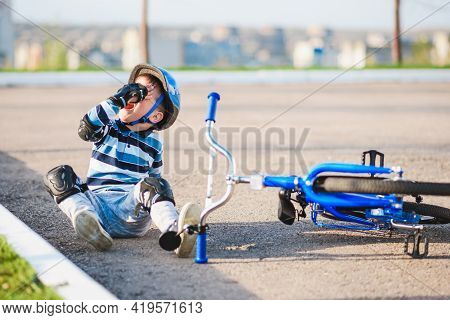 A Small Child Fell From A Bicycle Onto The Road, Crying And Screaming In Pain.