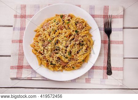 Penne Pasta In Tomato Sauce With Sausages And Cheese, Decorated With Parsley On A White Wooden Table