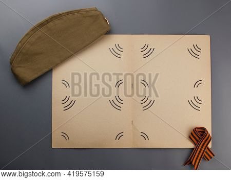 may 9 victory day holiday background. ribbon of St.George,old photoalbum and military cap - traditional symbol of Victory Day 1945. greeting card design. copy space
