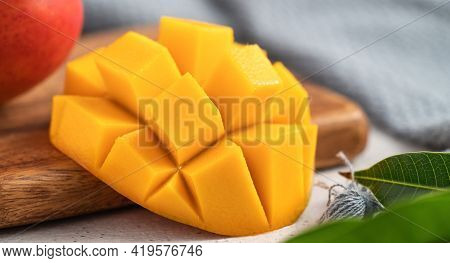 Diced Fresh Mango Fruit On A White Plate With Leaves.
