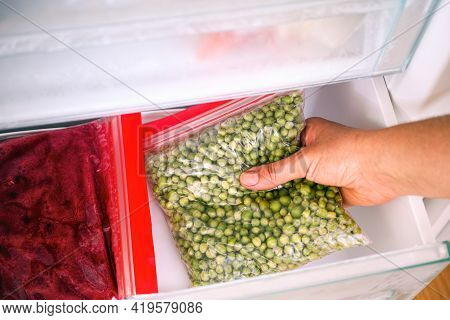 Woman Hand Taking Homemade Packing Of Green Peas Out Of Freezer. Close-up