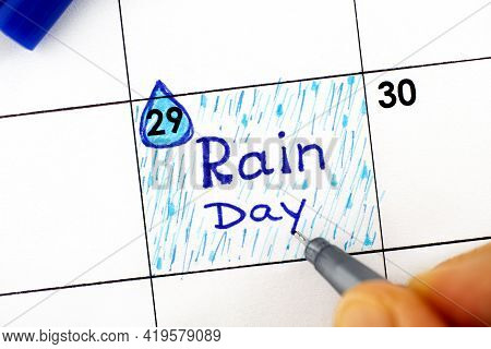 Woman Fingers With Pen Writing Reminder Rain Day In Calendar. July 29