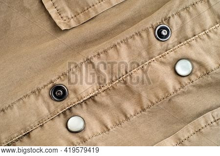 Close Up Of Buttons On Beige Jacket.