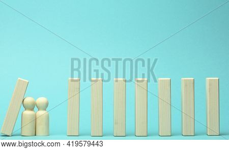 Figures Of Men Restrain The Falling Of Wooden Blocks, The Effect Of Dominoes On A Blue Background. C