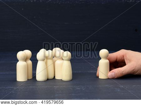 A Crowd Of Wooden Figures, Opposite The Hand Is Holding One Figure. Personnel Selection Concept, Sea