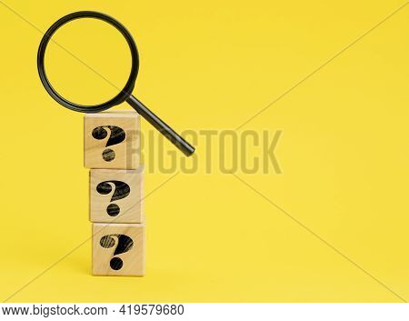 Wooden Cubes With Question Marks And A Magnifying Glass On A Yellow Background. The Concept Of Findi