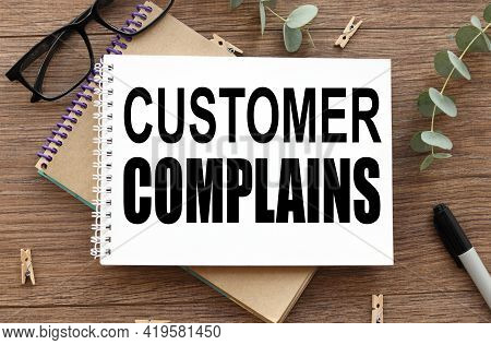 Customer Complaint. On A Wooden Background There Are Two Notepads Near Glasses And A Black Felt-tip