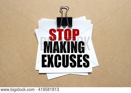 Stop Making Excuses .the Text On The Sticker. The Paper Is Clamped With A Clerical Clip. Paper On Wo