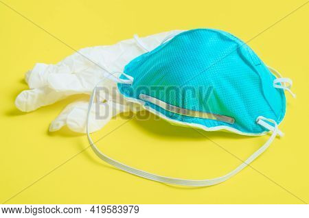 N95 Mask Or Respirators Masks And Disposable White Gloves On Yellow Background.