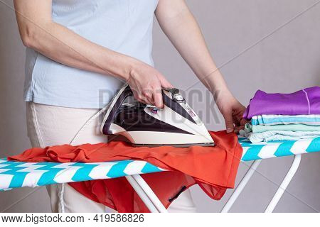 Close Up Of Woman Ironing Clothes On Ironing Board At Home