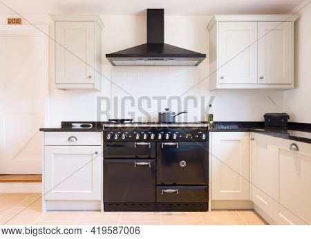 Modern Modular Kitchen Interior In Black And Off White, With Range Cooker And Chimney Extractor Hood
