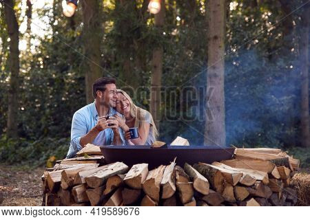 Romantic Couple Camping Sitting By Bonfire In Fire Bowl With Hot Drinks
