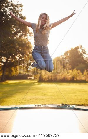 Portrait Of Woman In Mid Air Jumping On Trampoline Against Flaring Sun In Garden