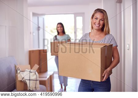 Portrait Of Female Couple Carrying Boxes Through Front Door Of New Home On Moving Day