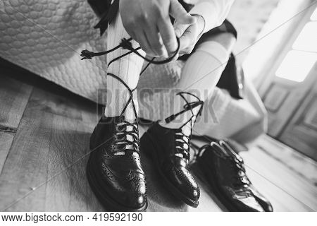 Preparing For A Scottish Wedding. Man In A Kilt And High Socks Sits On The Bed And Tie Long Shoelace