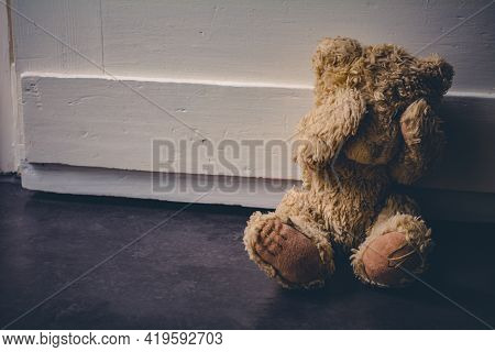 Abandoned Teddy Covering His Eyes, Sitting At A Door - Child Abuse Concept