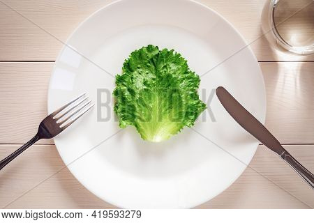 Green Lettuce Leaf On A Plate, Fork, Knife, Glass Of Water - Strict Diet Concept