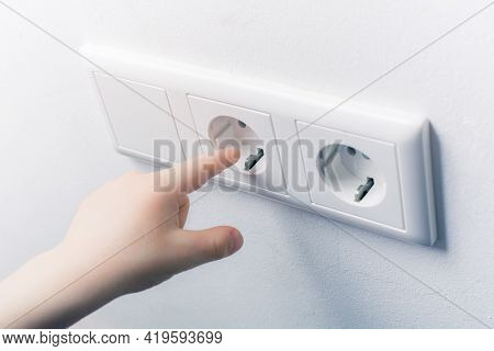 Child Tries To Touch A Wall Socket Without Safety Plugs - Prevent Child Hazard Concept