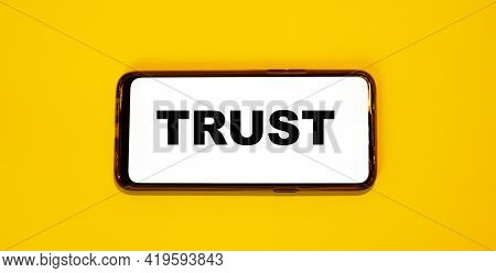Trust Concept On A Smartphone Screen On A Yellow Background. The Concept Of Trust In Modern Technolo