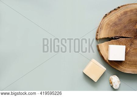 Natural Handmade Soap And Wooden Slab On A Green Background, Top View. Cleanliness And Hygiene Conce