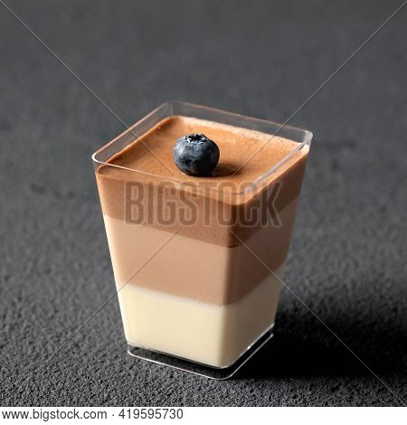 Mousse Triple Chocolate Dessert Or Jelly Decorated With Blueberry In Glass Cup On Black Background.