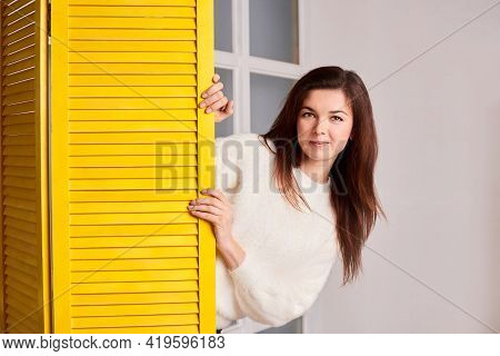 Front View Of Girl Peeping Out Of Yellow Screen, Looking At Camera