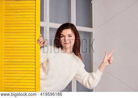 Friendly Woman Looking At Camera, Peeping Out Of Yellow Screen And Points A Finger Repairs