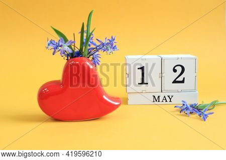 Calendar For May 12 : A Bouquet In A Heart-shaped Vase With Blue Flowers And The Numbers 12 On Cubes
