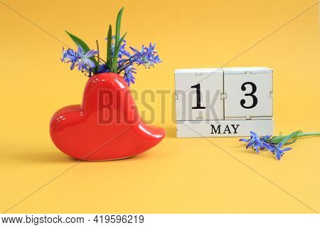 Calendar For May 13: A Bouquet In A Heart-shaped Vase With Blue Flowers And The Numbers 13 On Cubes,