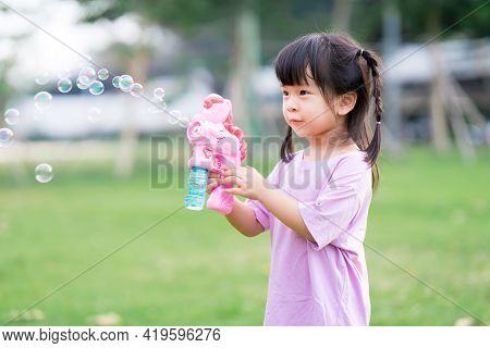 Happy Kid 4 Year Old Has Fun Playing With A Pink Bubble Gun. Child Is Excited By The Bubbles That Co