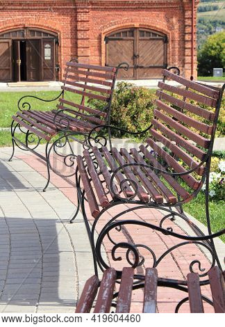 Wooden Benches With Wrought Iron Railings On The Playground