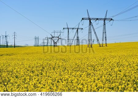 Scaffolding With A High Voltage Circuit In A Field Of Rapeseed And Blue Sky