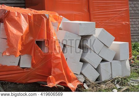 A Pile Of White Bricks And Foam Blocks In Red Plastic Cellophane Packaging On The Street