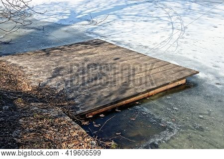 Brown Wooden Footbridge Near The Shore Over Gray Ice In The White Snow Of The Pond