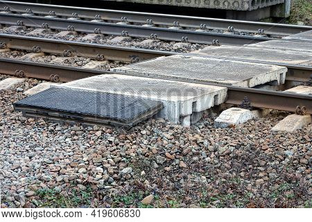 A Pedestrian Crossing Of Gray Concrete Blocks Lies On The Rails, Sleepers And Small Rubble Of The Ra