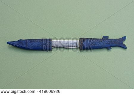 An Old Soviet Folding Knife With A Blue Handle In A Plastic Case In The Shape Of A Pike Fish Lies On