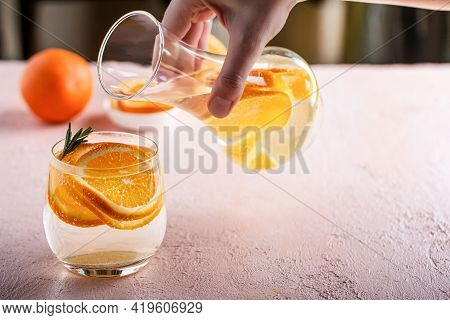 A Womans Hand Pours A Refreshing Detox Lemonade With Sliced Orange Into A Glass Tumbler On A Pink Ta