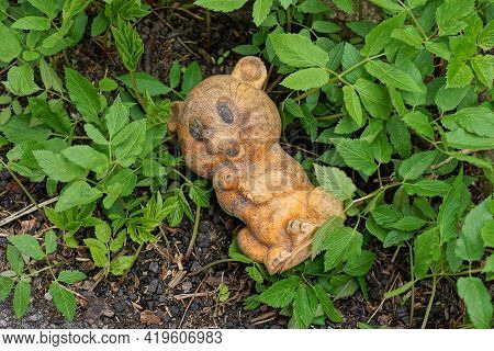 Garbage From One Brown Dirty Children's Rubber Toy Lies On Gray Ground Among Green Vegetation On The