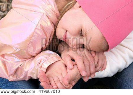 Grandmother And Granddaughter Holding Hands Together, Happy Granddaughter Touches Her Cheek To The G
