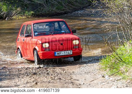 Madona, Latvia - May 01, 2021: Red Oldtimer Car Fiat 126 Overcomes Water Obstacle